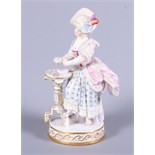 A late 19th century Meissen porcelain figure of a standing woman in 19th century costume by a tripod