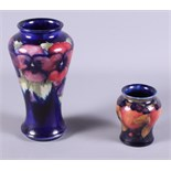 """An early 20th century Moorcroft pottery Pansy vase on a midnight blue ground, 7"""" high, together with"""