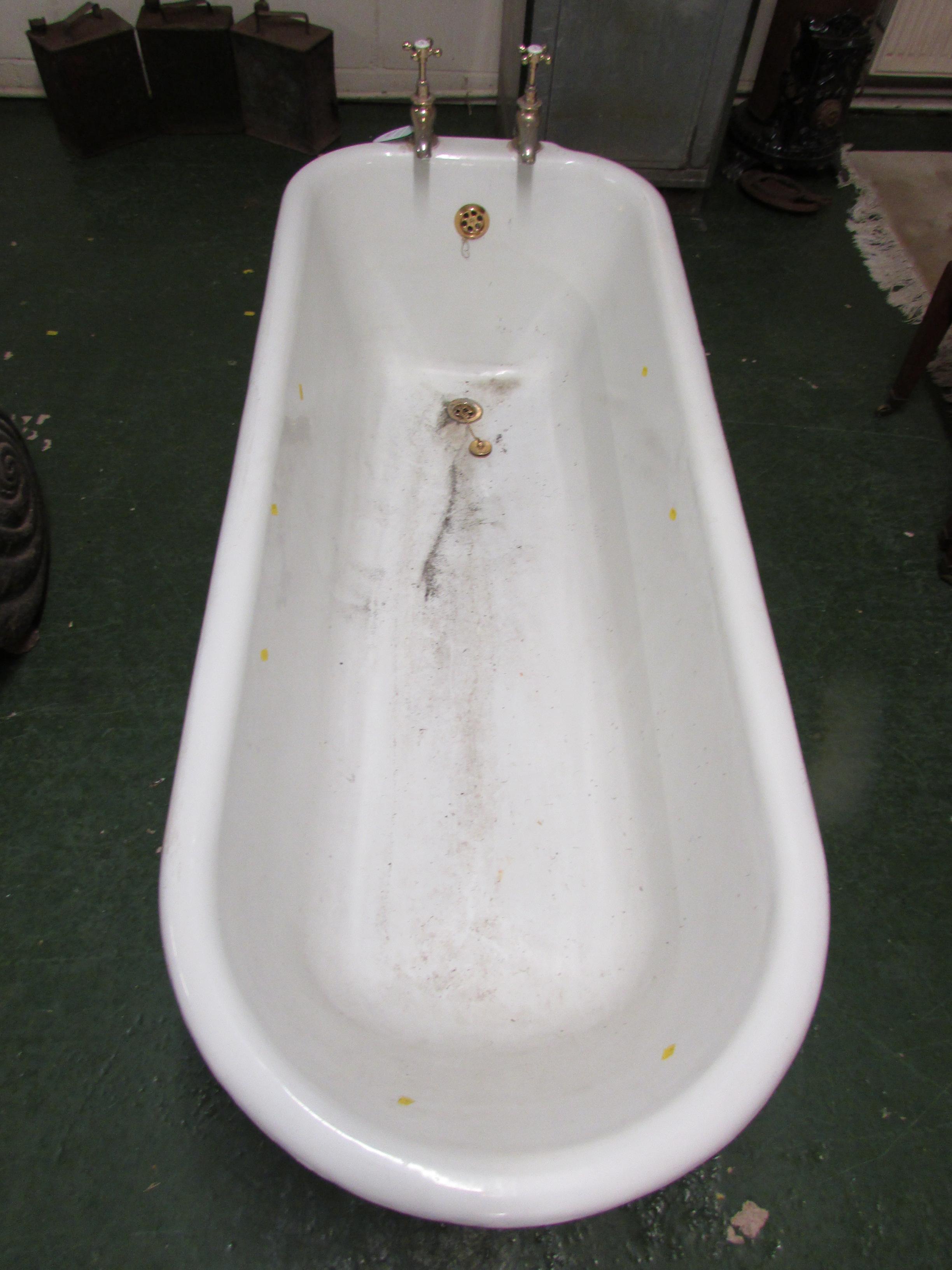 Lot 34 - Cast iron enamel bath, white to the interior, black to the exterior, raised on four feet and