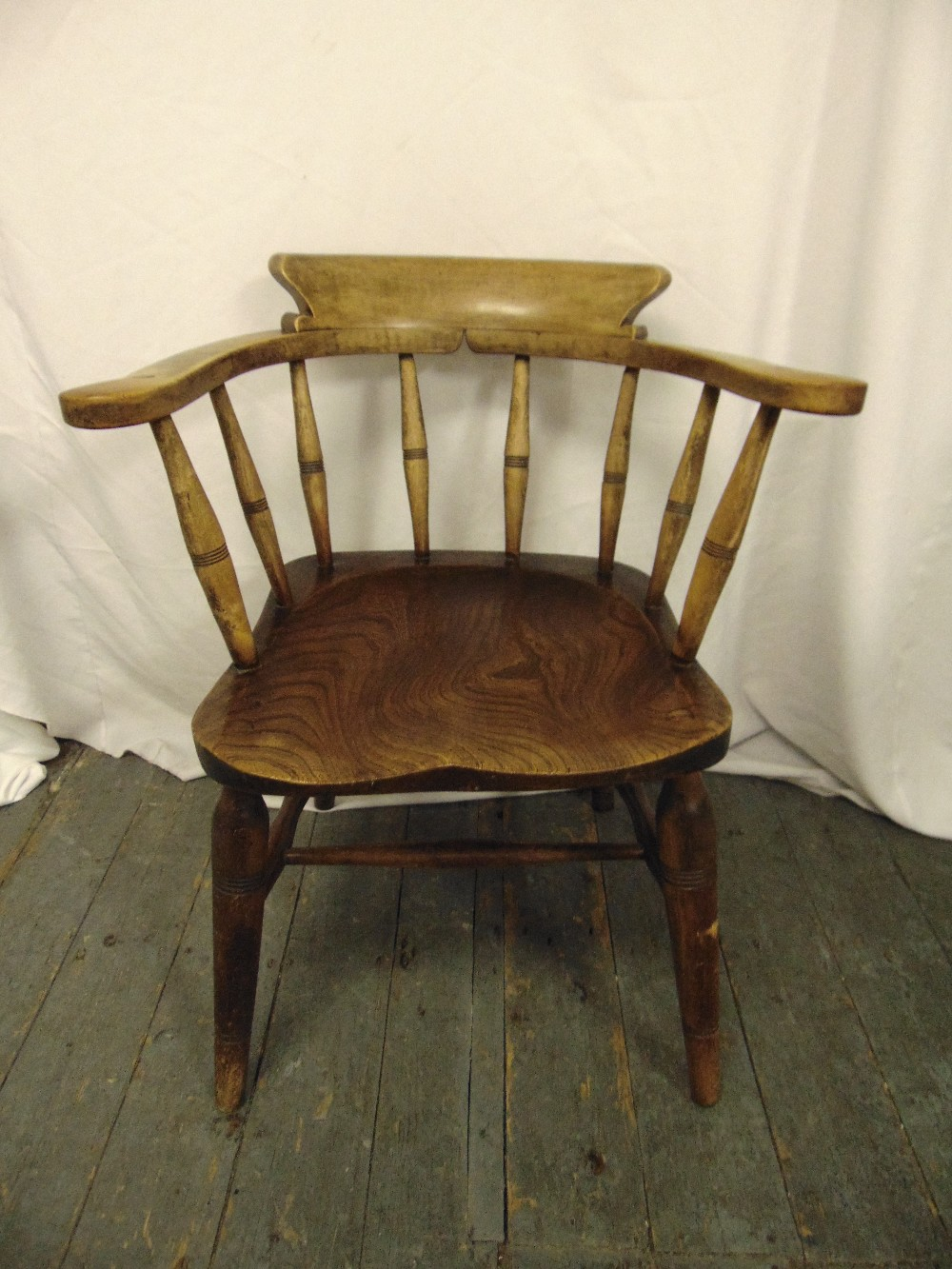 Lot 31 - An elm Windsor chair of customary form with turned spindles on four turned legs
