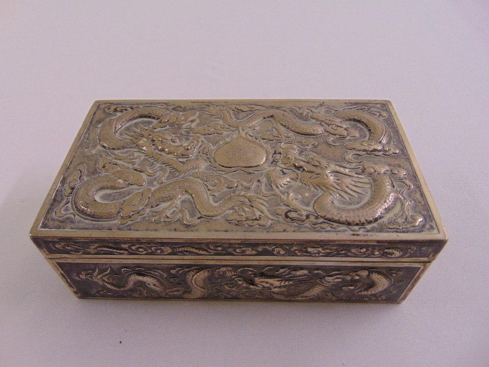 A Chinese white metal rectangular casket profusely chased with dragons to the sides and hinged
