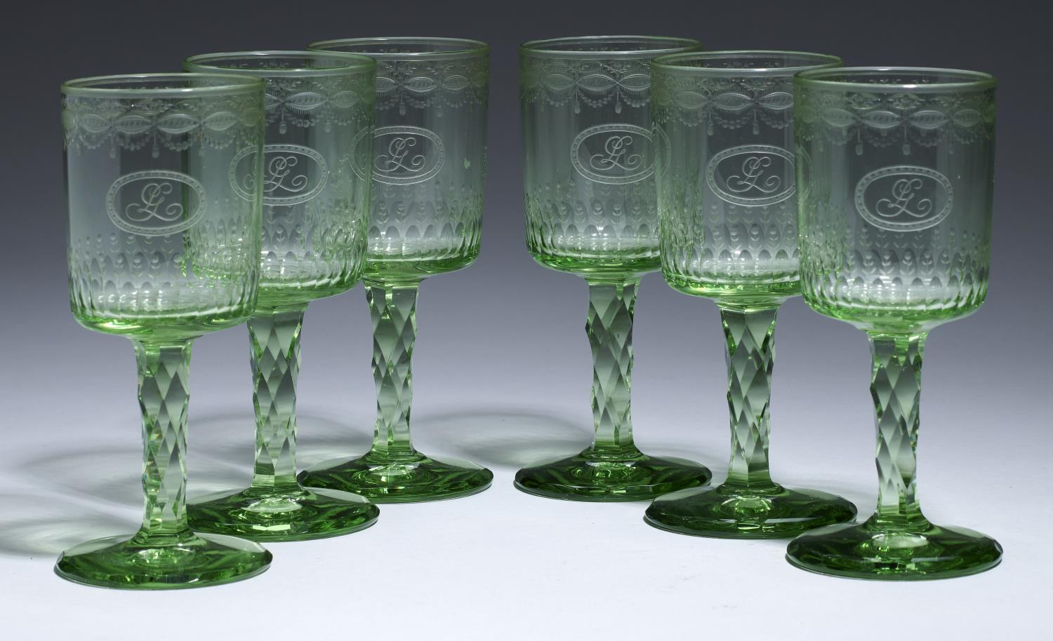 Lot 369B - A SET OF SIX GREEN GLASS WINES, C1910 the fluted bucket bowl engraved with monogram and festoons,