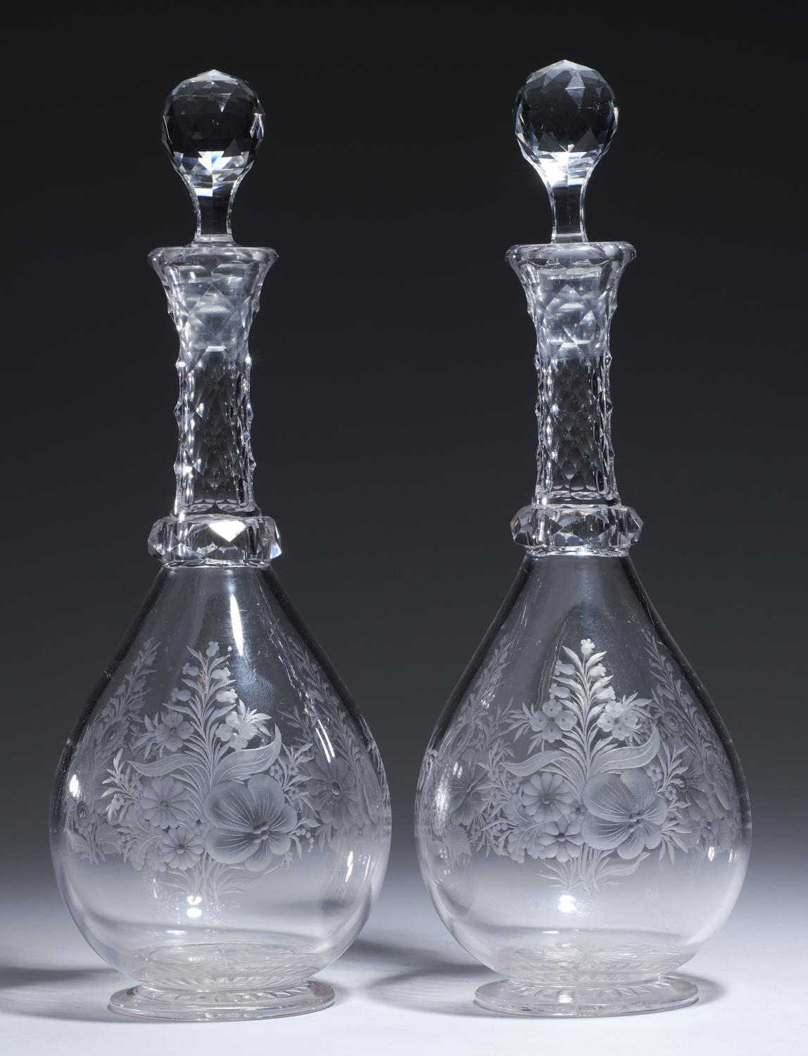 A PAIR OF ENGRAVED AND CUT GLASS DECANTERS AND STOPPERS, EARLY 20TH C with faceted neck and