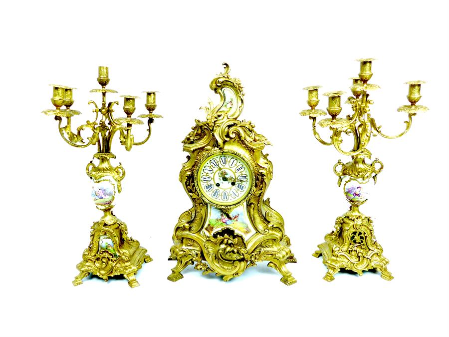 Lot 59 - A Rococo style gilt metal and porcelain clock garniture