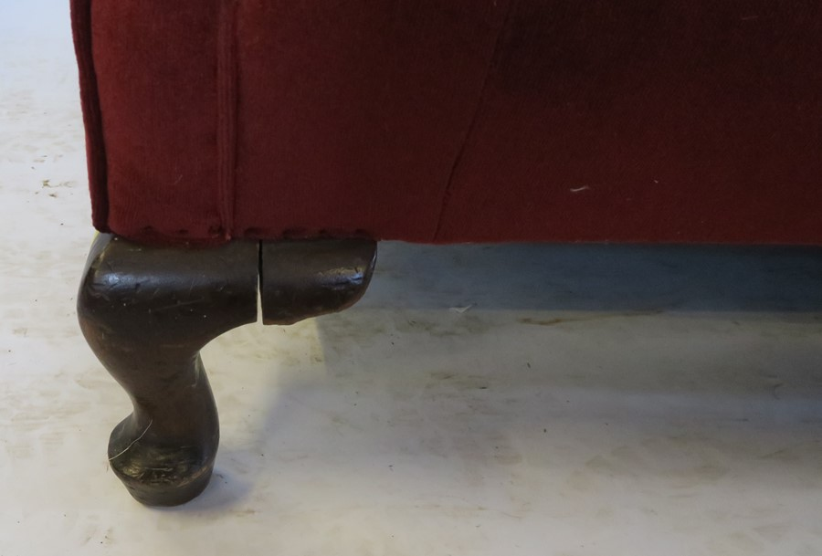 Lot 19 - A red upholstered settee, with serpentine back rail. raised on short cabriole front supports, length