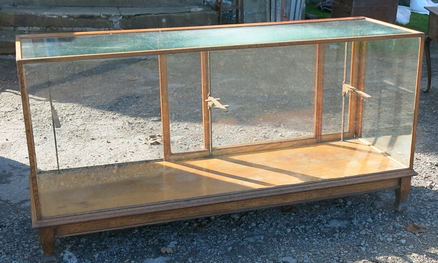 An oak and glass shop play counter, with sliding doors and shelves, 70ins x 23ins x 35.5ins