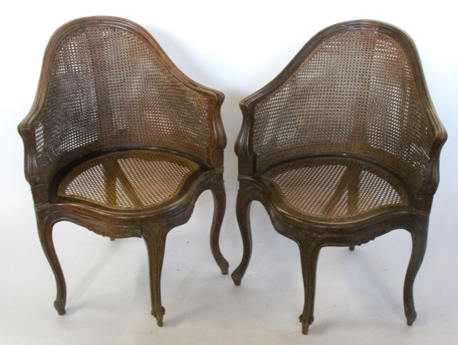 A set of seven bergere dining chairs, with shaped front rail, raised on craved scroll legs