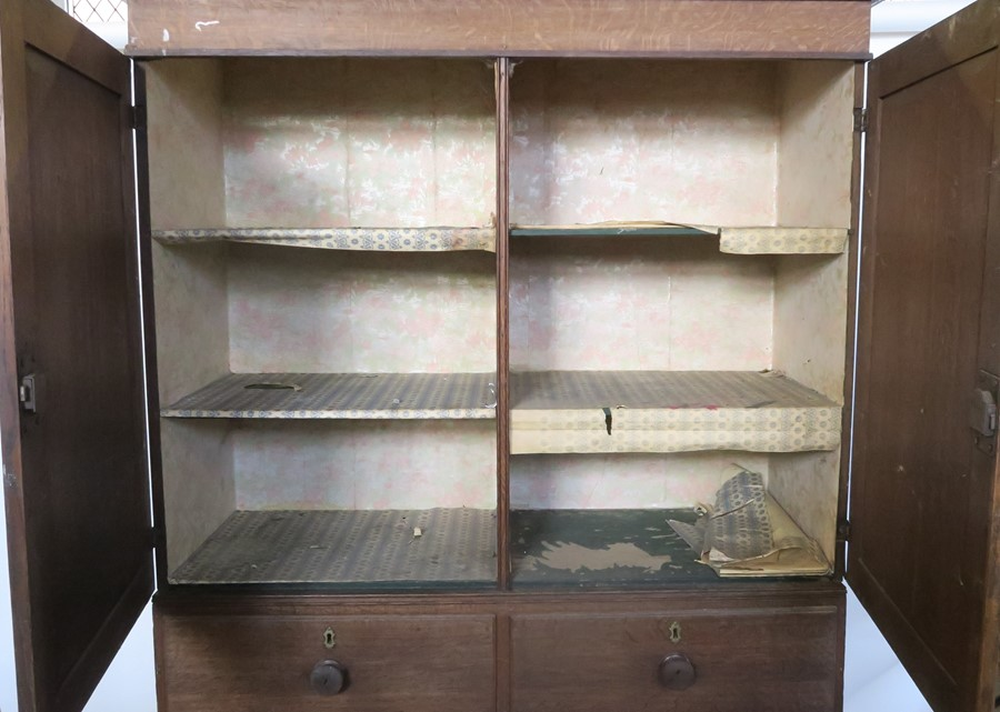 Lot 29 - A 19th century oak linen press, the cupboard fitted with shelves, the base with two short over three