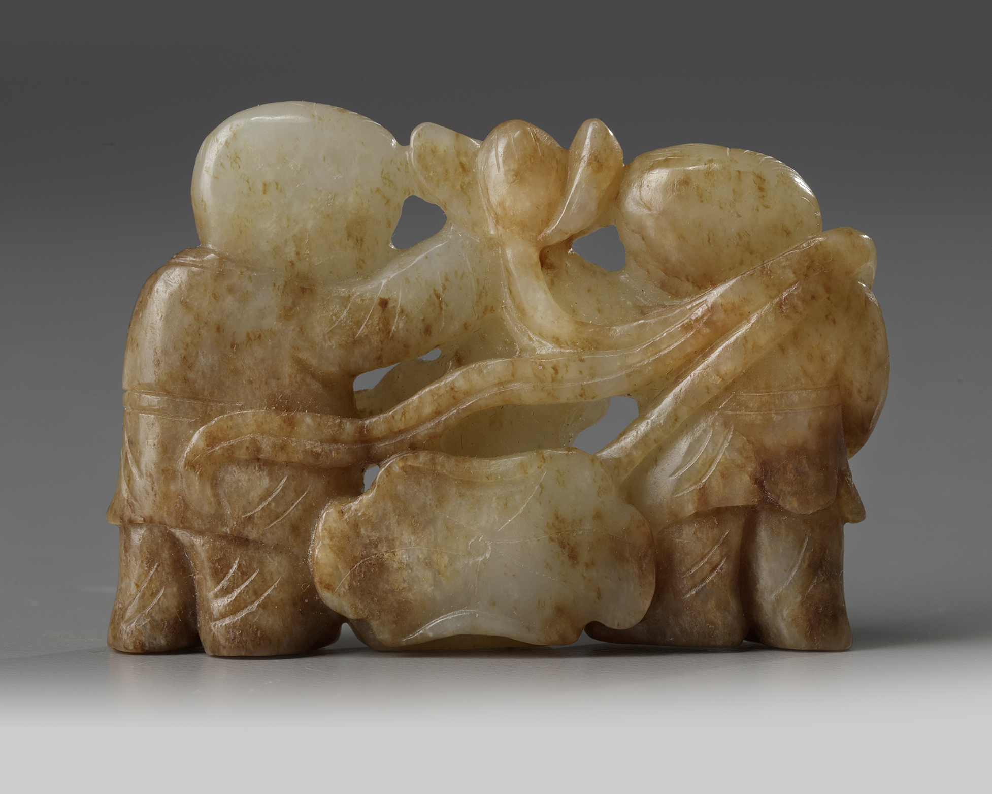 Lot 54 - A Chinese celadon and russet jade 'Hehe Erxian' carving