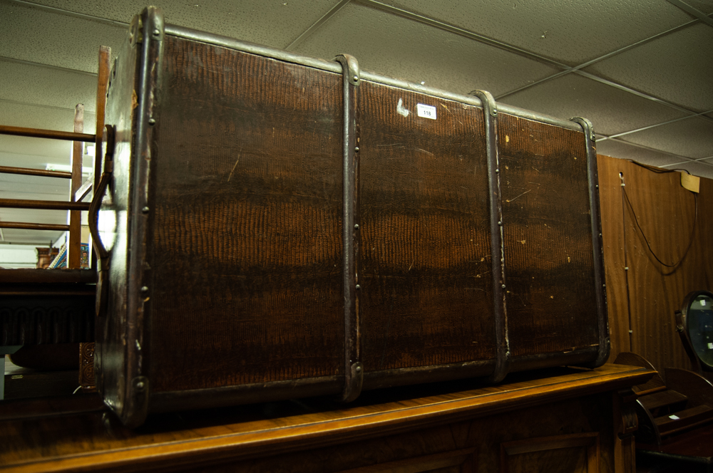 Lot 118 - A LEATHER BOUND TRAVELLING TRUNK, WITH END HANDLES