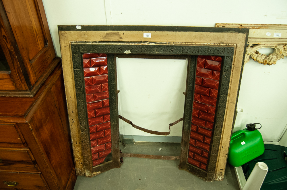 Lot 131 - LATE VICTORIAN/EDWARDIAN CAST IRON AND FACETED RED GLAZED CERAMIC TILE INSET FIRE SURROUND
