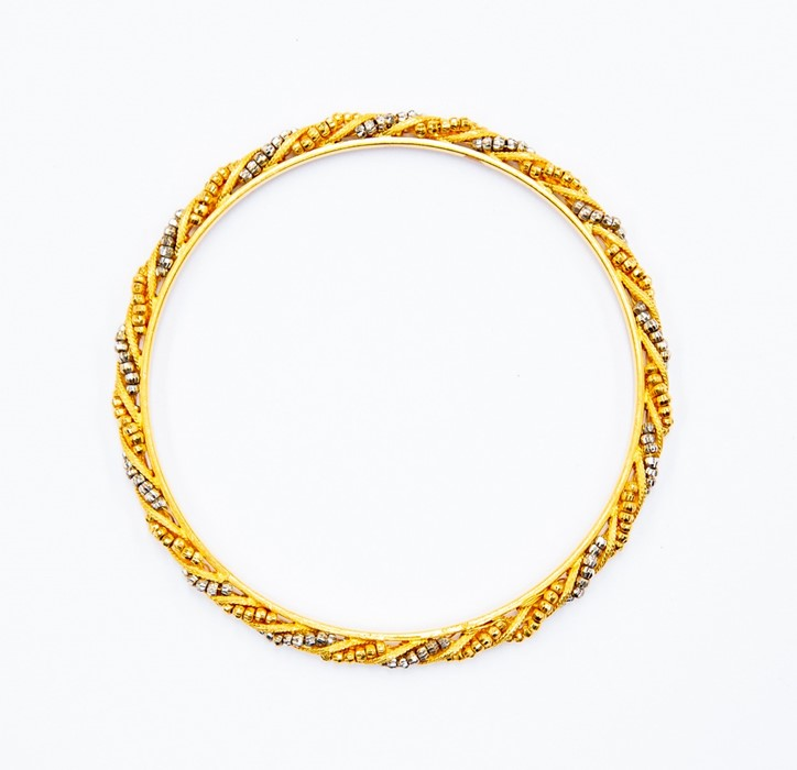 Lot 253 - A yellow and white metal continental bangle, alternate swirling rows of yellow and white bead