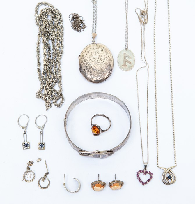 Lot 149 - A silver and amber dress ring; a silver heart shape pendant set with rubies; a silver cuff bangle
