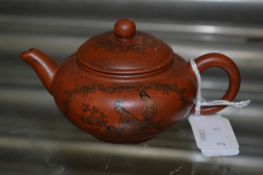 A clay Chinese teapot depicting erotic scenes.