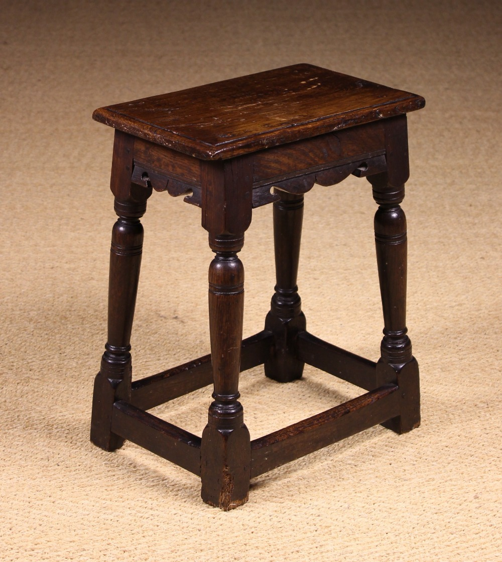 Lot 59 - An 18th Century Oak Joint Stool having a moulded top above serpentine rails on rising baluster legs