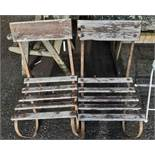 A pair of old wrought iron framed garden chairs with wooden slat seating