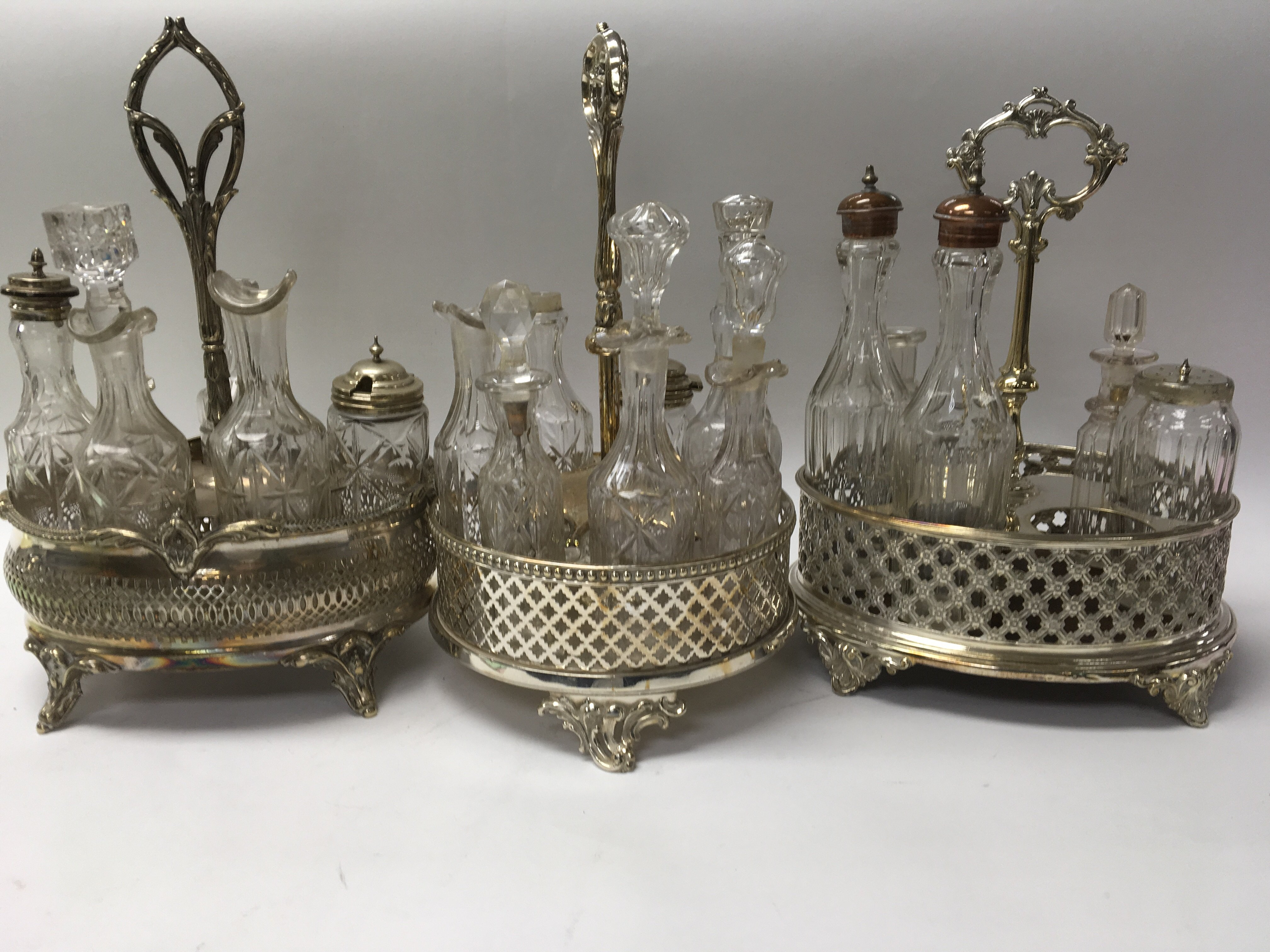 Lot 247 - Three silver plated cruet stands inset with bottle