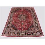 A Meshed woollen hand-made carpet with dark red ground, 134 by 97ins. (340 by 245cms.) (see