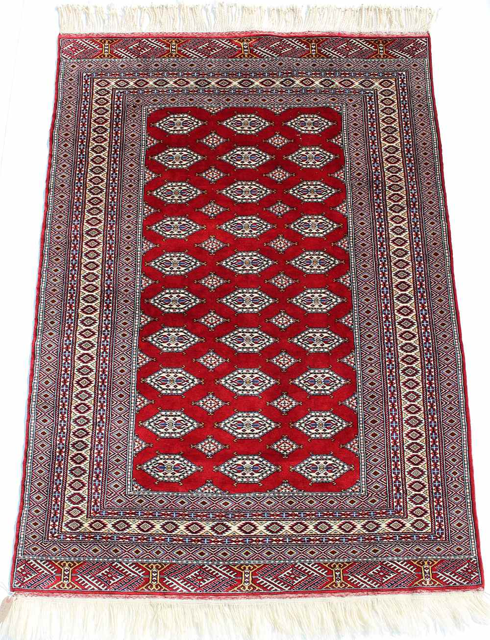 Property of a lady - a Turkoman rug with burgundy field, third quarter 20th century, condition