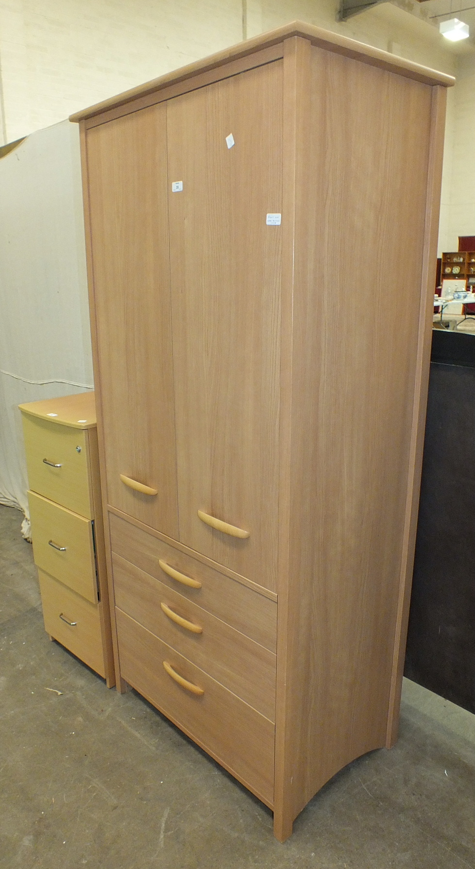 Lot 35 - A modern wood finish three-drawer filing cabinet and a modern teak finish wardrobe, (2).