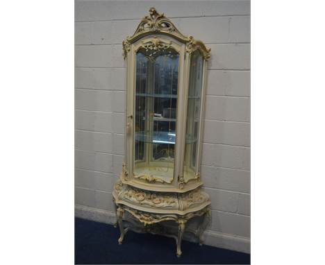 A SILIK BAROQUE STYLE ITALIAN SINGLE DOOR CURIO CABINET, with heavily carved ornate decoration, with rounded glass panels enc