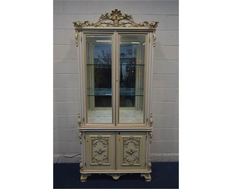 A SILIK BAROQUE STYLE ITALIAN TWO DOOR DISPLAY CABINET, with heavily carved ornate decoration, with bevelled glass panels enc