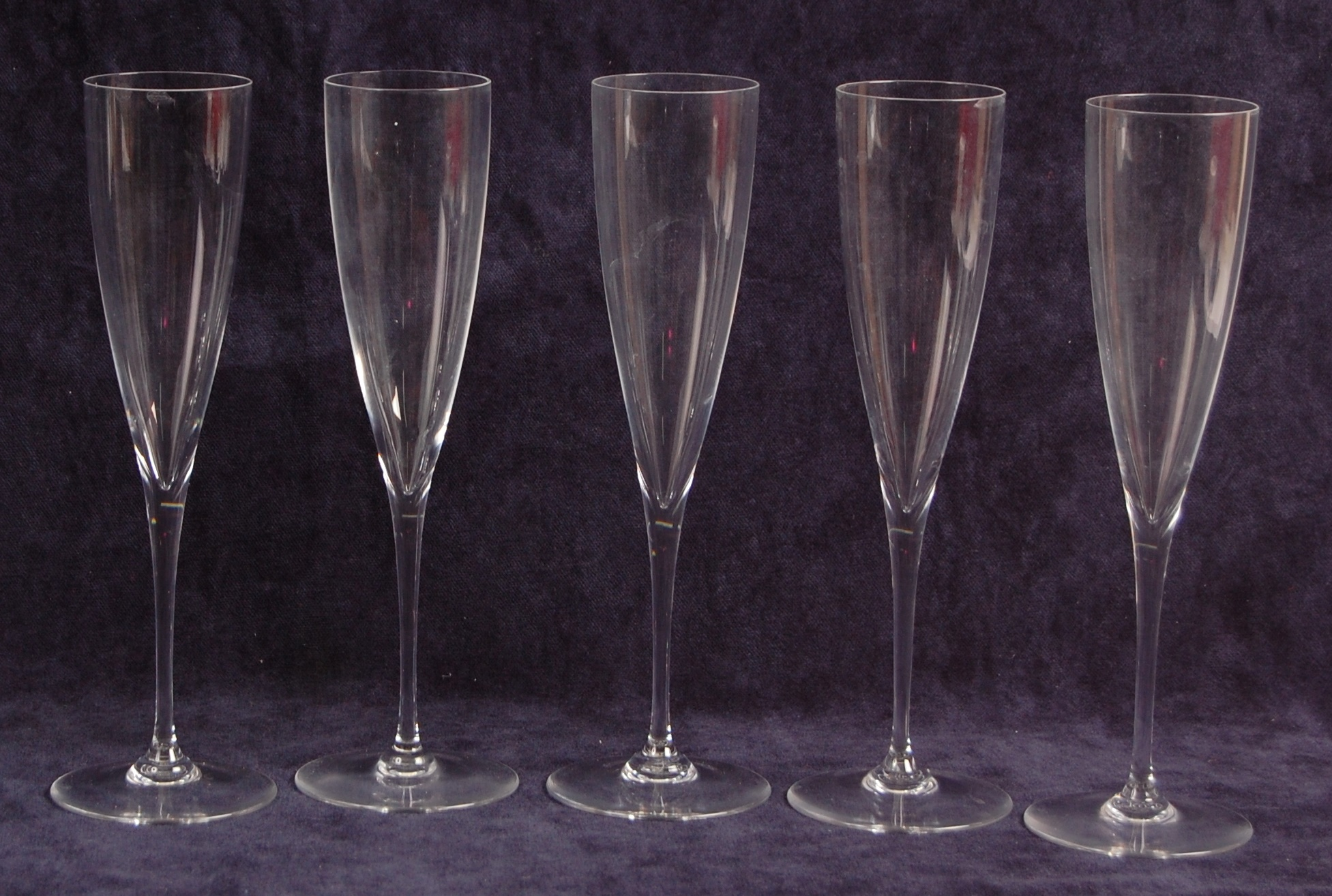 A set of five Baccarat crystal glass champagne flutes, of plain tapering long stemmed form, each