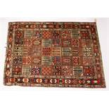 A PERSIAN RUG, 20TH CENTURY, the central field with five rows of eight panels depicting flowers