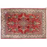 A PERSIAN ISFAHAN CARPET, red ground with central medallion, urns of flowers in a conforming