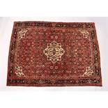 A PERSIAN RUG, 20TH CENTURY, red ground with central medallion, within a dark blue border. 6ft 10ins