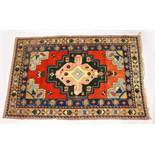 A PERSIAN RUG, 20TH CENTURY, bright red ground with large stylised design, within a similar double
