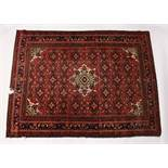 A PERSIAN RUG, 20TH CENTURY, red ground with central medallion, within a dark blue border. 6ft