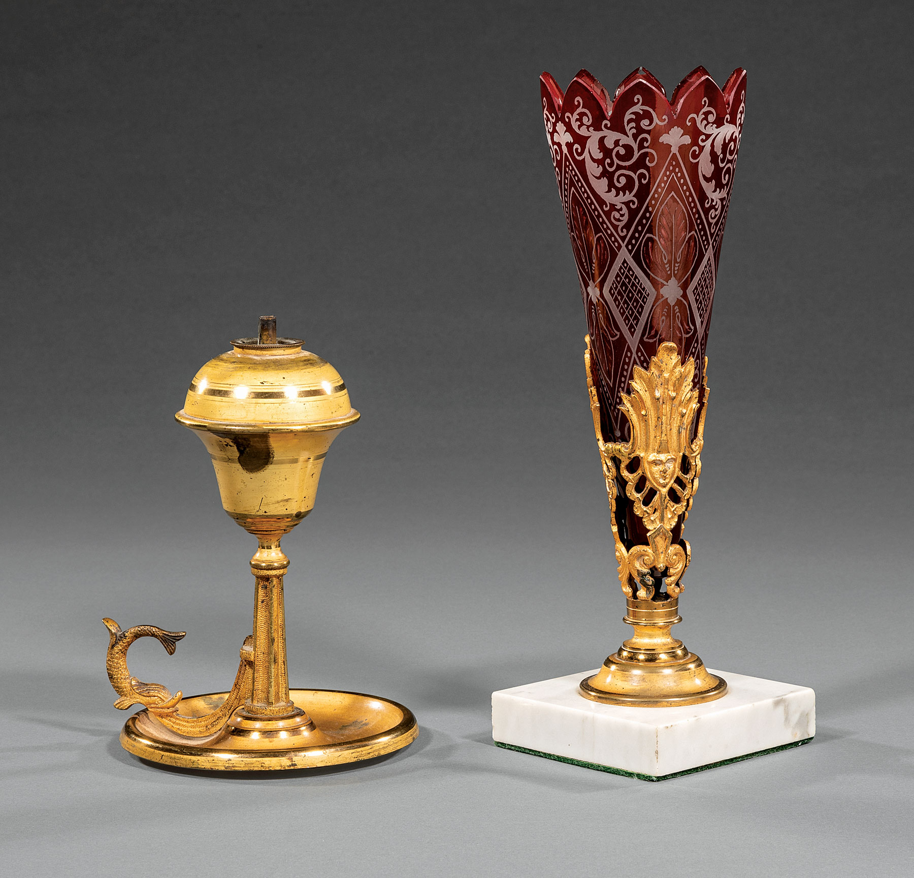Lot 649 - American Gilt Brass Chamberstick , 19th c., dolphin handle, matte and burnished surface, h. 7 in.;