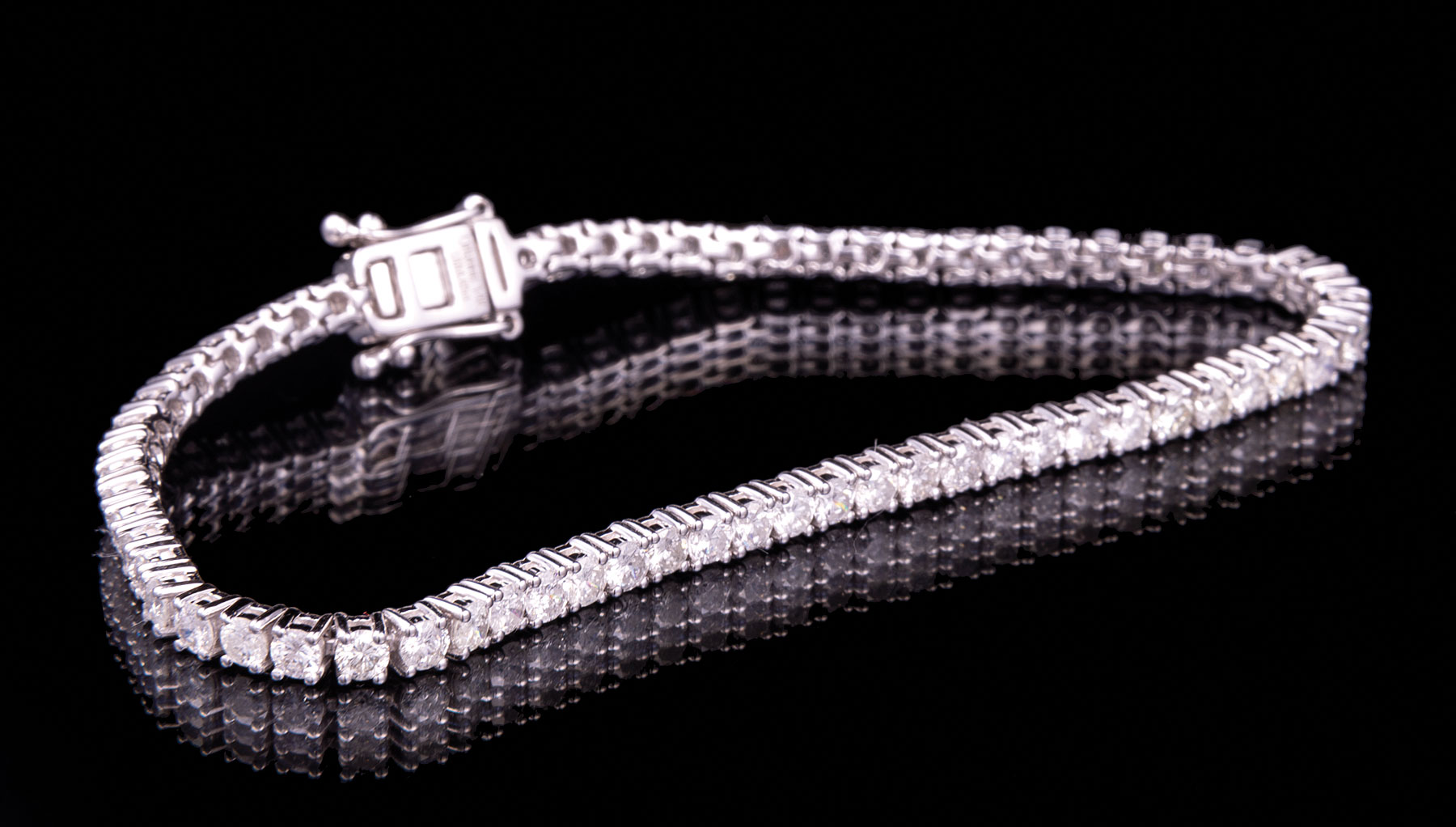 Lot 602 - 14 kt. White Gold and Diamond Tennis Bracelet , 64 prong set round brilliant cut diamonds, total wt.