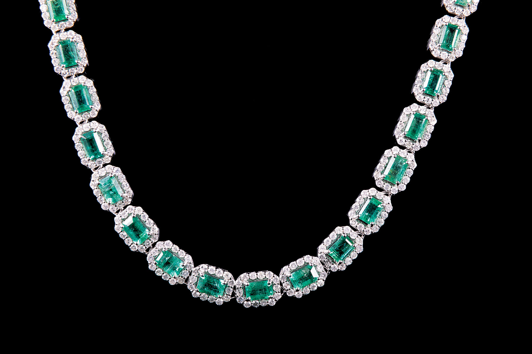 Lot 579 - 14 kt. White Gold, Emerald and Diamond Necklace , 41 prong set rectangular step cut natural