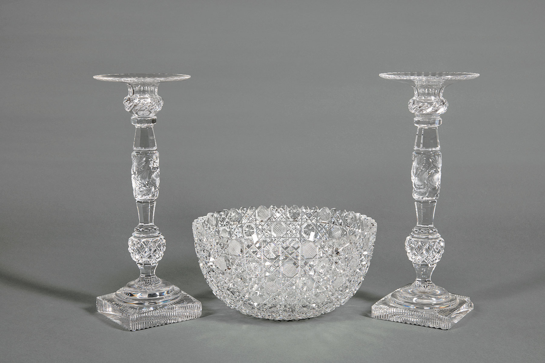 Lot 992 - Pair of Cut Crystal Candlesticks and Bowl , h. 12 1/2 in. and h. 5 in., dia. 10 in . Provenance: