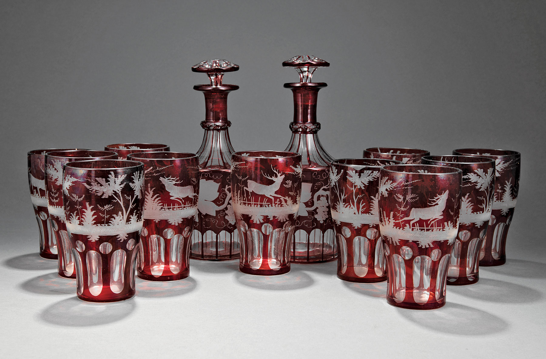 Lot 764 - Set of Eleven Bohemian Ruby Cut-to-Clear Glass Tumblers , decorated with deer in forest scenes, h. 5