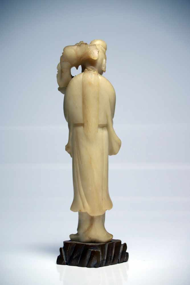 Lot 12 - White GuanyinJadeChina19th ctH: 28 cmStanding Guanyin holding a lotus flower over his left