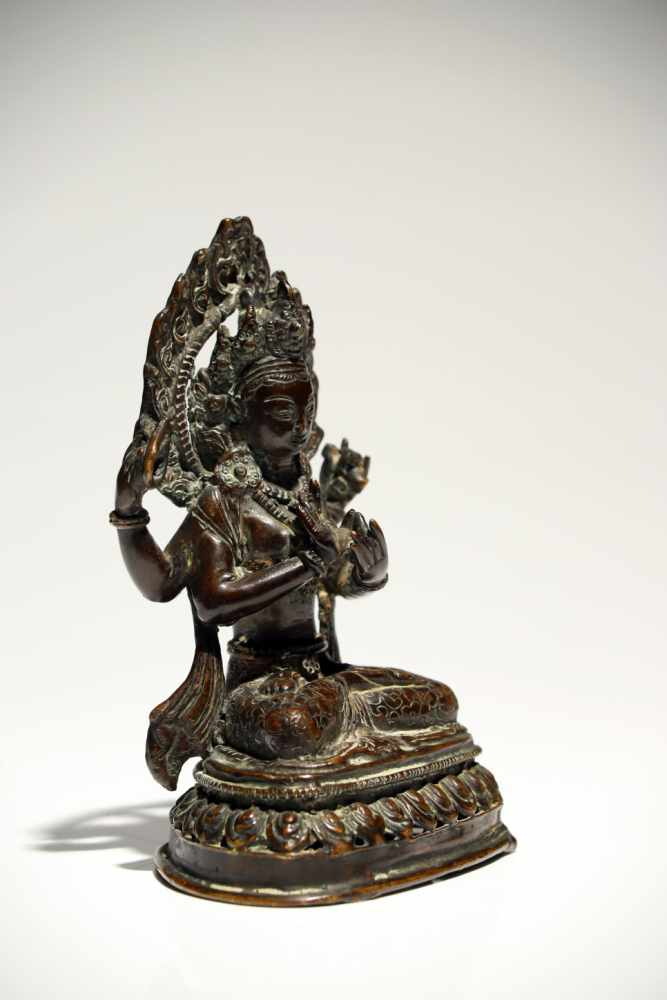 Lot 10 - ShadakshariBronzeTibet19th ctH: 16 cmAvalokiteshvara Shadakshari sitting in padmasana (lotus pose)