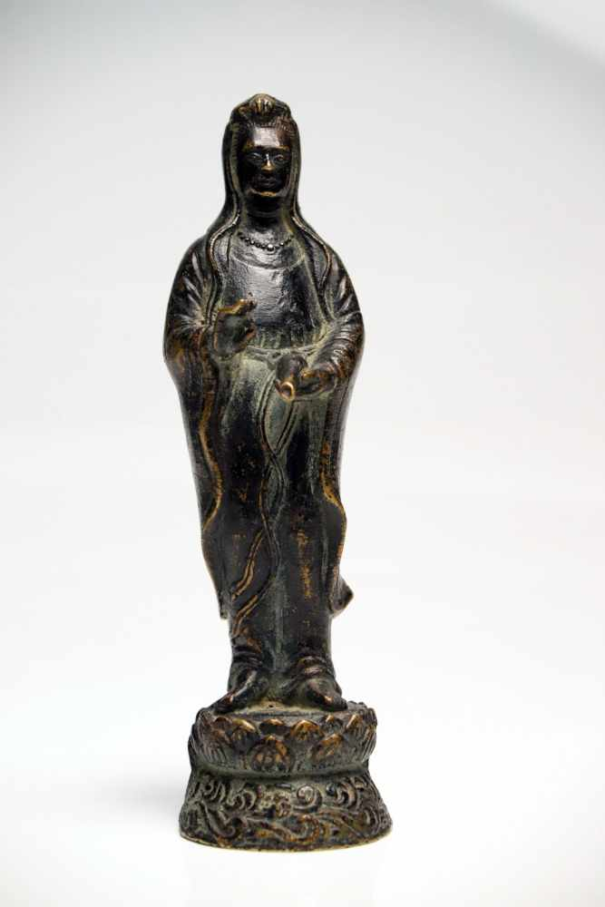 Lot 8 - GuanyinBronzeChina19th ctH: 20 cmStanding Guanyin on lotus base holding a vase in the left hand to