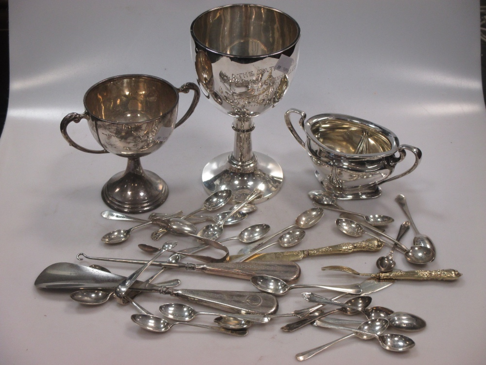 A silver presentation engraved trowel, two silver trophies, together with a silver sugar bowl,