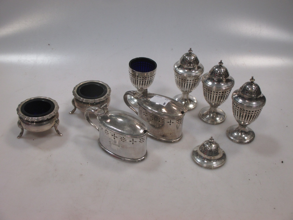 Four silver pierced pepper casters, together with a pair of open salts and a pair of mustards all