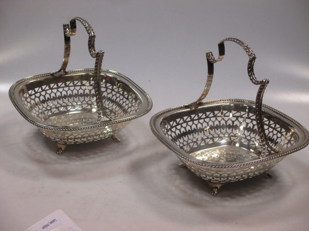 A pair of George V silver fruit baskets, with pierced sides and fixed scroll handles, raised on