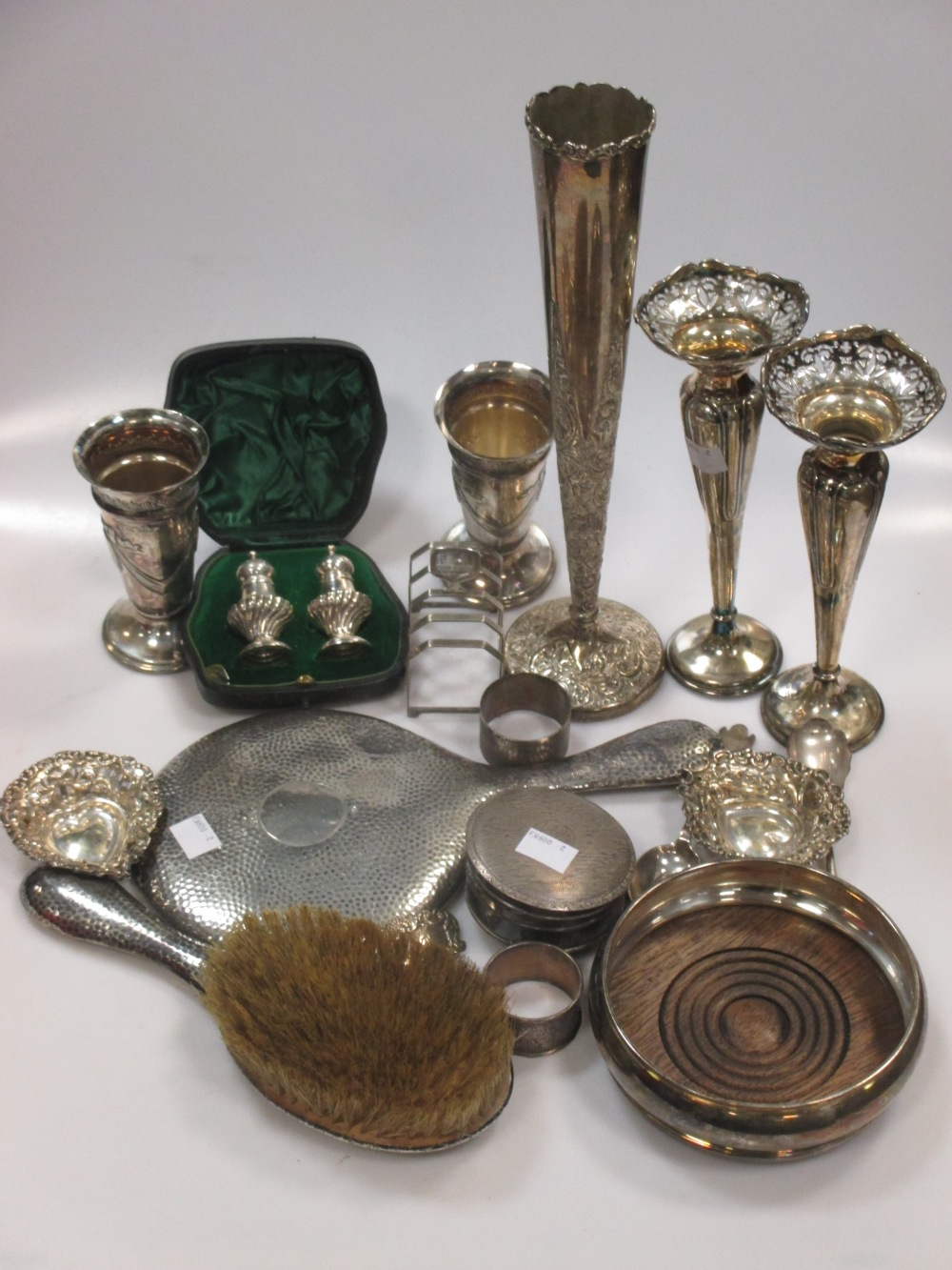 A collection of silverware including five vases, a bottle coaster, pin trays, toastrack cased pair