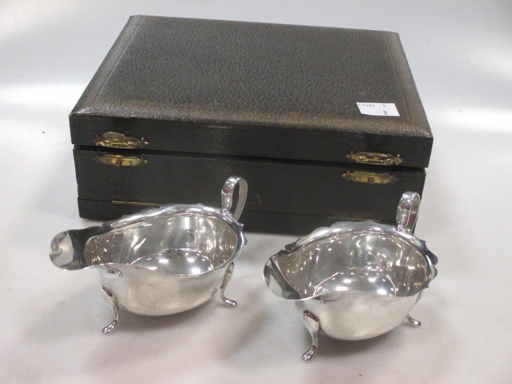 A matching pair of silver sauce boats in a presentation case, 3.3ozt gross (2)
