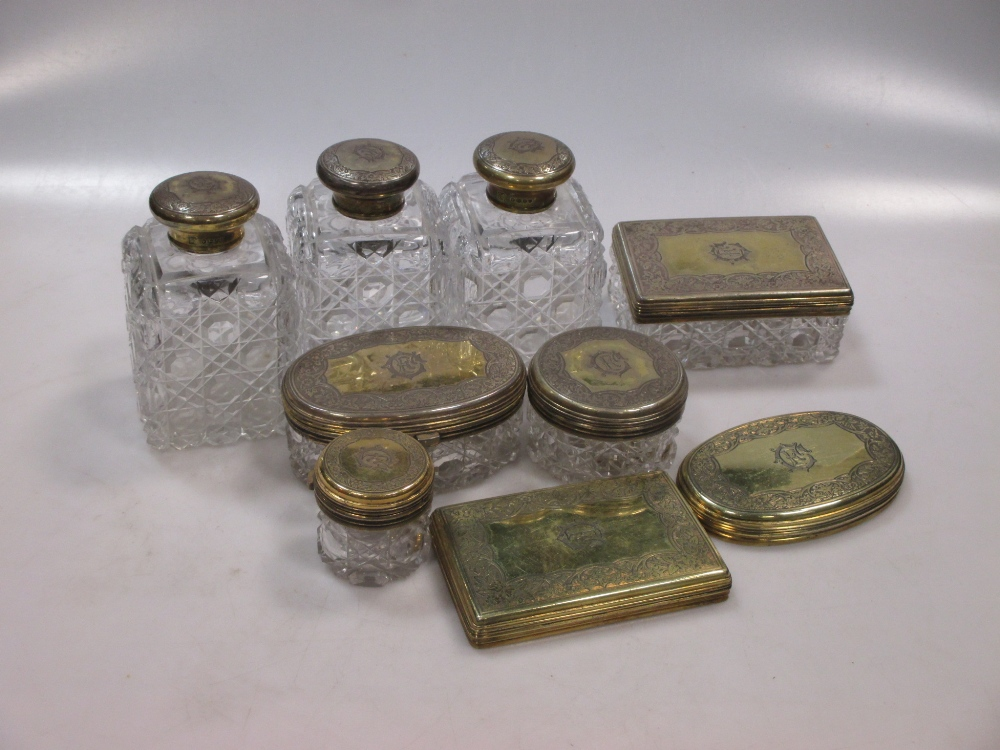 Lot 391 - Asprey - A Victorian silver ten piece lady's toilet set, with cut glass bodies and gilded covers,