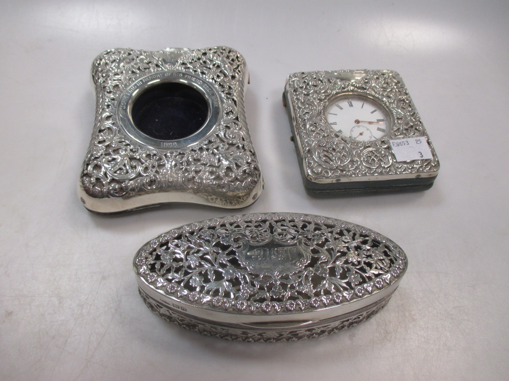 Two silver embossed watch holders, one with a plated watch together with a silver fretted oval