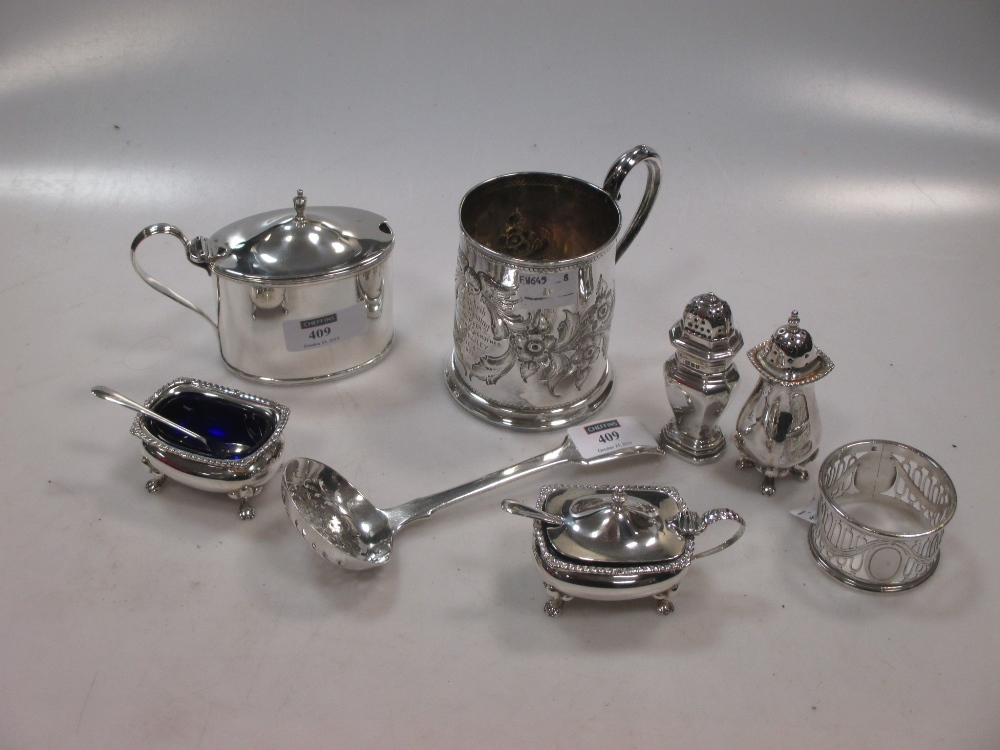 A collection of silverware including a condiment set, a mustard, a christening mug, a napkin ring, a