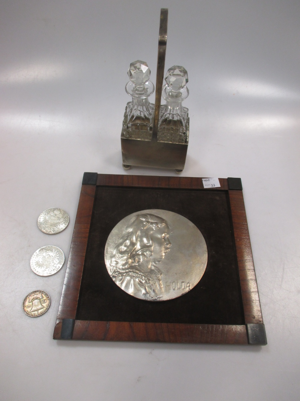 A Continental silver cruet set with a pair of glass bottles, three silver coins and a plated