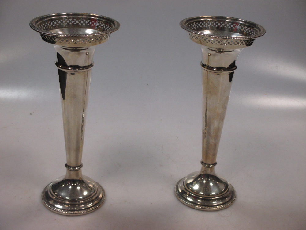 A pair of silver trumpet vases with cupped necks and pierced rims